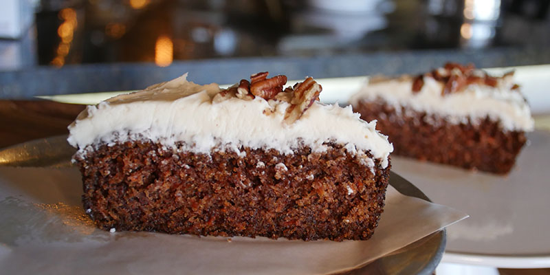 Two slices of carrot crunch cake on plates.